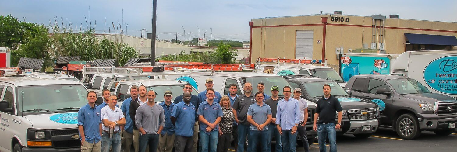 elite heating and air conditioning team photo with 20 people 10 company trucks and office building in very back